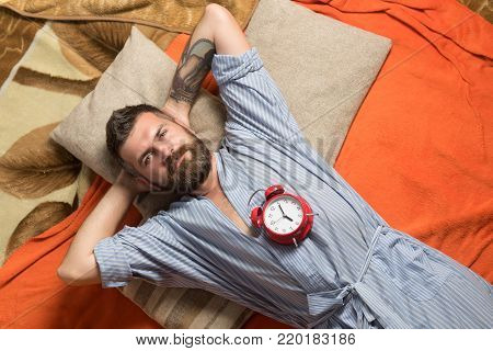 Time management, perfect morning. Man with clock in bedroom, loneliness. Relax and wake up, time. Tired hipster with clock. Bearded man sleep on floor with alarm clock.