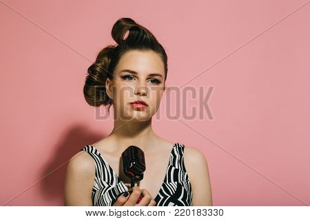 Pin up young girl on pink background, radio. Woman singer with stylish retro hair and makeup. Beauty and vintage fashion. Girl in glasses sing in microphone. Music, look and retro style, pinup.