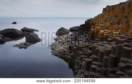 The Giant's Causeway is an area of about 40,000 interlocking basalt columns, the result of an ancient volcanic eruption. It is located in County Antrim on the north coast of Northern Ireland, about three miles northeast of the town of Bushmills