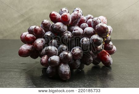A bunch of red variety of grapes on a wooden table.