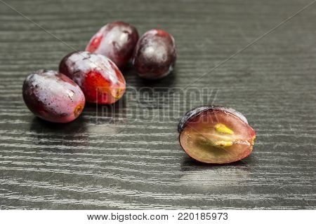 Cut red grape on a wooden table and a few whole fruits in the background.
