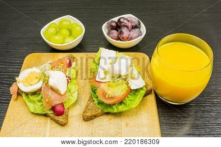 Sandwiches with vegetables, eggs, cheese and salmon, and grape and a glass of orange juice. That is a tasty and nutritious breakfast.