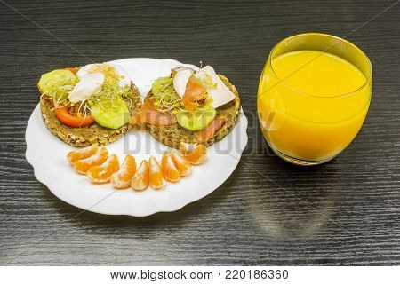 Breakfast for a child. Smiling face with healthy food on a plate and orange juice to drink.