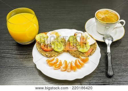 Breakfast before work. A cheerful face made of sandwiches and fruit on a plate. Drinking orange juice and hot fresh coffee.