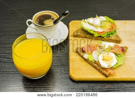 A quick breakfast before work. Healthy sandwiches with vegetables, fish and eggs. Drinking orange juice and hot fresh coffee.