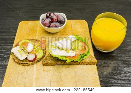 A healthy and nutritious breakfast. Board with sandwiches and grapes in a bowl. Drinking juice from freshly squeezed oranges.