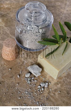 Jar of medical mud, organic soap, and olive branch
