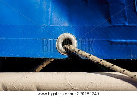 old rusty eyelets on an aged blue coated plastic canvas for agricultural and temporally use hanging in a