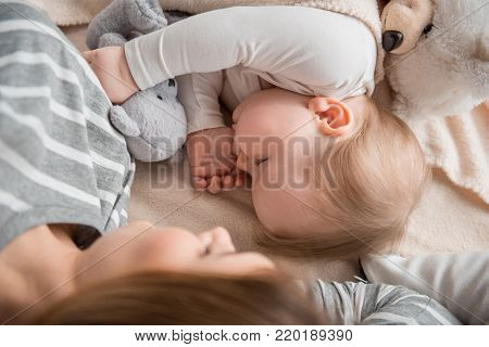 Top view of innocent baby sleeping close to mom. Focus on baby sucking her thumb