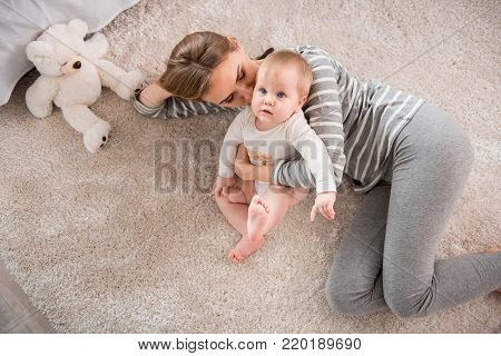Top view of affectionate mother lying with little daughter on carpet. She is hugging and kissing her suckling