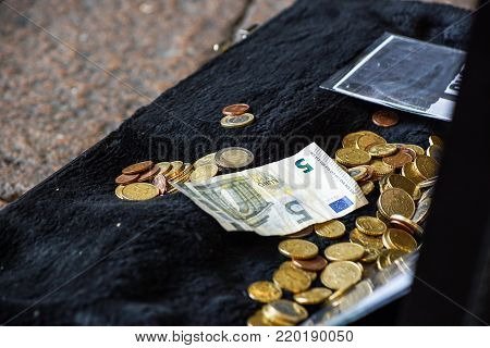 Hand throwing money in the old hat from a street artist, finance concept, selected focus, narrow depth of field