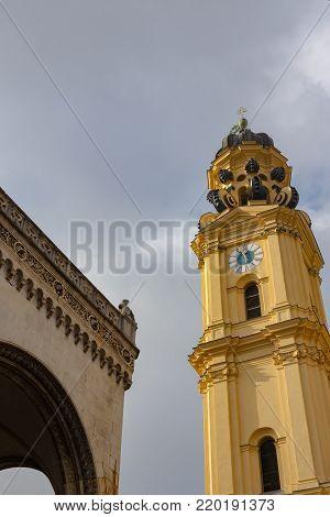 feldherrnhalle and tower of theatinerkirche theatinerchurch at odeon square odeonplatz in munich city bavaria germany tower clock time detail portrait orientation