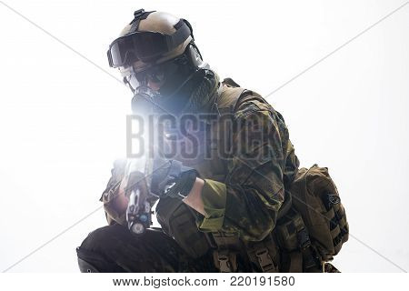 Portrait of soldier looking at sniper scope of weapon. War concept. Isolated