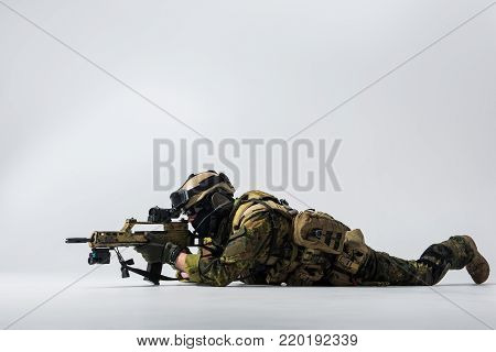 Full length side view serene peacemaker looking at sniper scope of assault rifle while locating at ground. Army concept. Copy space