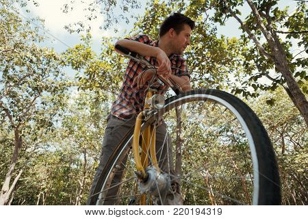 A young man is tired of riding a bicycle. It's hot outside and he wants to drink. The concept of the inconvenience of traveling by bike