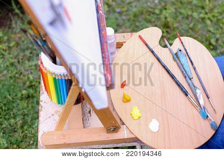 Photo depicts wooden easel on which stands white canvas with painting started, Wooden palette with paints and bank decorated with colored pencils which stands with brush located in park outdoors. Concept of art materials, oil or acrylic paint, professiona