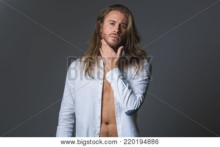 Waist up portrait of bearded stylish man in unbuttoned blouse. He is looking at camera with equanimity. Isolated on grey background