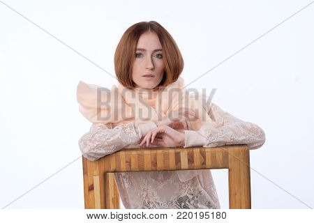 The red-haired girl is playfully posing in a lace blouse and a translucent scarf sitting on a wooden chair. . Her legs are bent at the knees, Hands - on the elbows. Grace, thoughtfulness