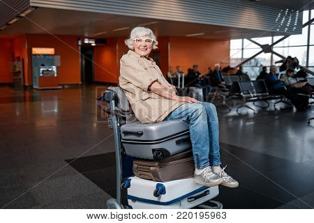 Have fun. Full length portrait of cheerful gray-haired lady is sitting on airport trolley with suitcases. She is looking at camera with joy while waiting for boarding at terminal lounge