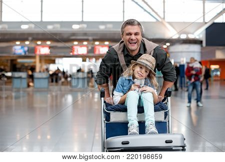 Joyful start of journey. Portrait of happy mature father is pushing airport trolley with suitcases and his adorable daughter who is sitting on it. They are looking at camera with smile. Copy space