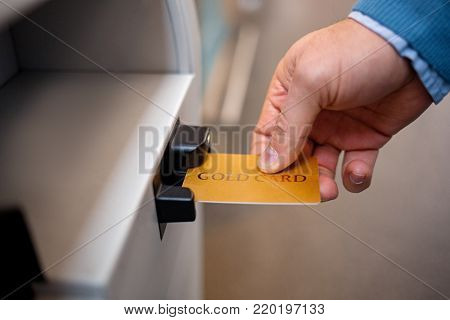 Payment process. Close-up of male hand is keeping gold credit card in airport hall. He is going to pay for his flight tickets using self-service check-in kiosk
