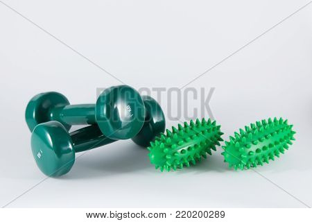two small green weights for fitness training recreation and two green hand massage tools for thrombosis prevention physio therapeutic