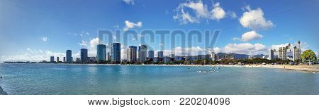 Panoramic of Ala Moana Beach Park with office building and condos in the background during a beautiful day on the island of Oahu, Hawaii.