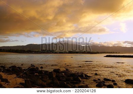 Beautiful Dusk over the ocean with waves moving to rocky shore at Hale'iwa Beach Park on the North Shore of Oahu with mountains in the distance.