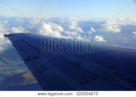 Aerial high in the sky shot of window view of plane leaving Honolulu, Hawaii with the wing of a commercial jet plane with large ship in the water and Hawaii Kai, beach, and Portlock of Oahu visible.
