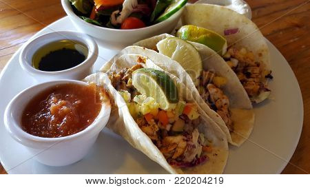 ISLAND FISH TACOS: blackened island fish, flour tortilla, mixed cabbage, black bean, chipotle aioli, tropical fruit salsa, red salsa, sour cream and side salad on wood table