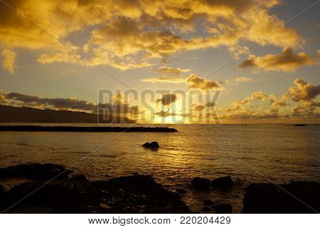 Beautiful Sunset over the ocean along rocky shore at Hale'iwa Beach Park on the North Shore of Oahu.