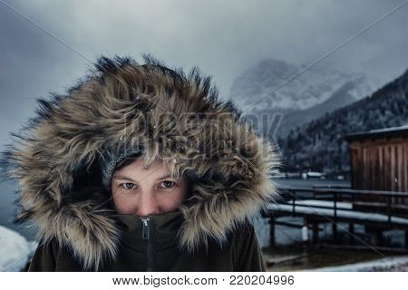 Female portrait. Adventurer woman outdoors. Lifestyle picture. Woman in warm clothes looking at camera, Fur hoodie. Beautiful scenery on background. Focus on people.