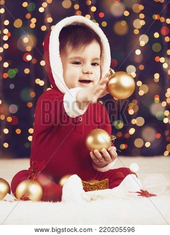 little child boy dressed as santa playing with christmas decoration, dark background with illumination and boke lights, winter holiday concept