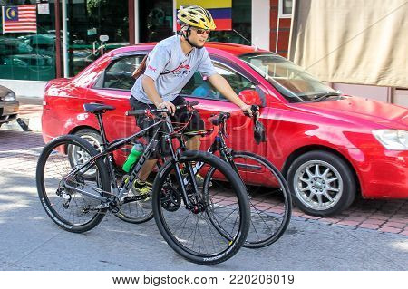 Labuan,Malaysia-Sep 30,2017:Young man wearing cycling yellow helmet carrying two bicycles by cycling in the city street at Labuan island,Malaysia.