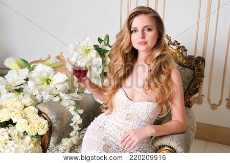 Elegant blonde lady with glass of wine in restaurant. Beautiful sexy young woman with long hair perfect body and pretty face make-up wearing evening dress drinking alcohol in light luxury interior.