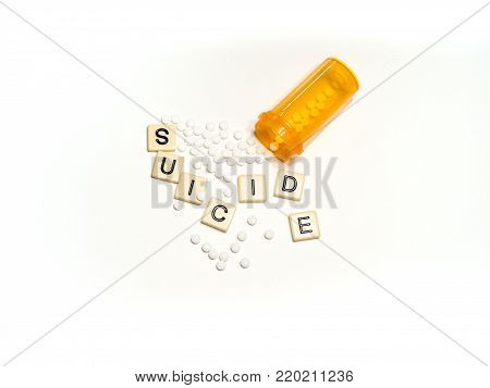 Suicide spelled with scattered tan tiles with an prescription bottle and white oxycodone pills spilling out. Photographed from above on a white background. Image has copy space.