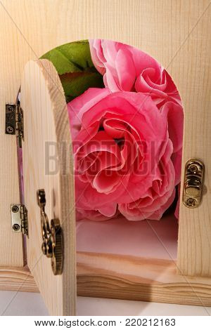 wooden door and pink flowers for valentine day in the background