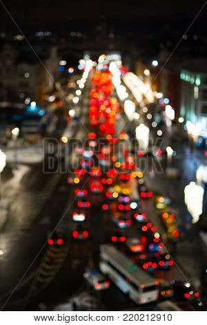 Aerial view of city road with cars in traffic jam, out of focus lights during the night. Colorful street lights background.