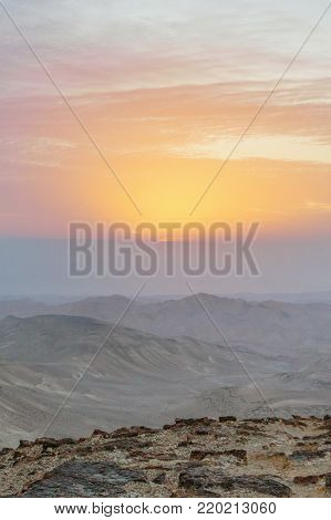 Vertical photo amazing red sunrise landscape in negev desert israel. Colorful outdoor view on rocks mountains sand, sun and clouds. South nature scene. Tourism in national park