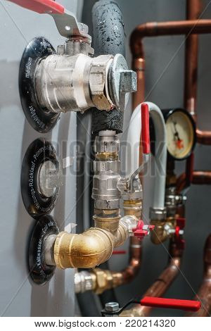 Valves and copper pipes on a boiler in a boiler room. Close up.Word on boiler