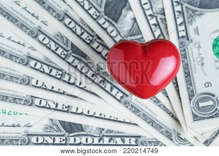 Shiny red heart on pile of US Dollar banknotes using as business money lover or valentines' day gift.