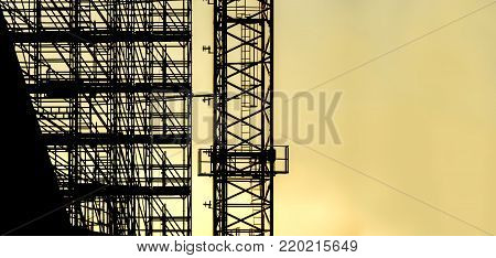 silhouette scaffolding with copy space for text, building construction, black profile structure of scaffolding warm orange colors sunset, construction, architecture engineering