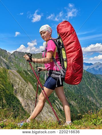 Hiking. Traveler with large backpack walks along edge of pass using trekking sticks for balance. Free tourism in mountains of Eastern Siberia