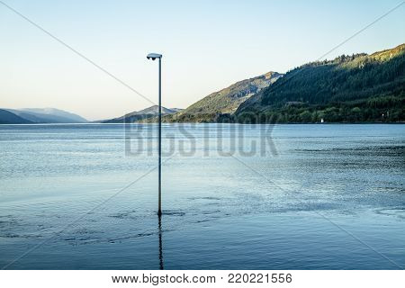Lake is flooding a lamp post at Loch Linnhe, Scotland