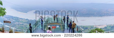 Nong Khai ,Thailand - December 26 , 2017 : Tourists  visit the popular glass skywalk on cliff by Mekong River at Wat Pa Tak Sua