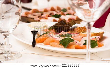 Diced butter, caviar, black bread. Bowl of red fish with spoon served with sliced bread, butter and herbs on white background. Wholegrain bread, butter and red salmon fish, white background