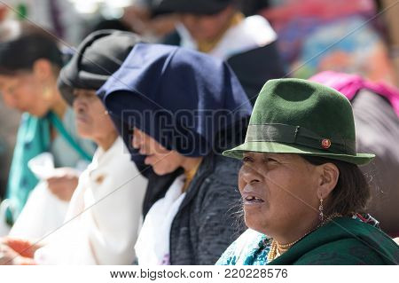 Otavalo, Ecuador-December 23, 2017: indigenous people sitting outdoors in the local market