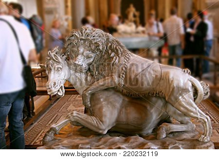Lion hunting. Ancient sculpture of a lion viciously attacking a horse, in the Vatican museum, Rome, Italy. poster