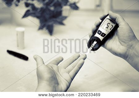 A medical test, checking a drop of blood on the sugar level. Pierce the finger with a lancet.