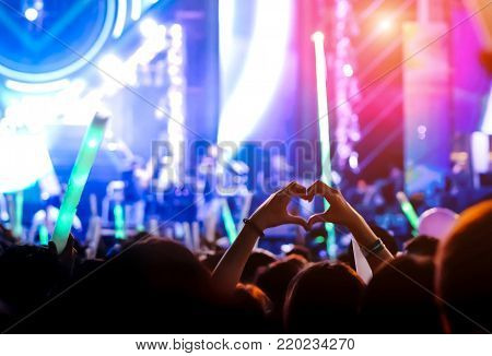 Hand gesture loves finger at concert stage lights crowd or audience artist band in the music festival rear view with spotlights glowing effect and people fan audience silhouette make heart shaped raising hands up